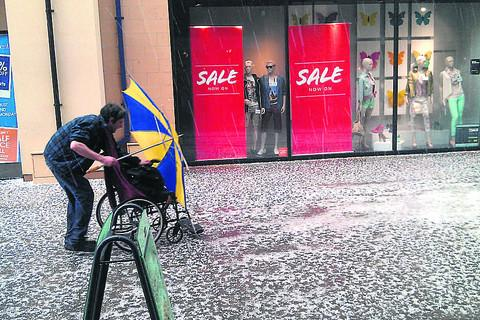 A shopper struggles to make progress as a hailstorm hits Witney