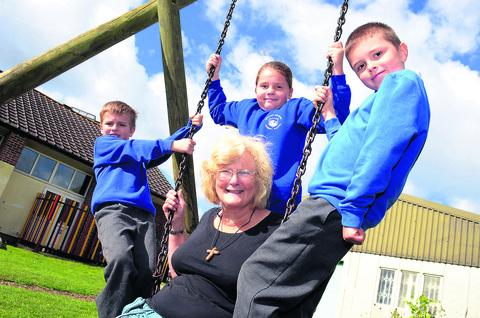 Sue Price at the Blackbird Leys Adventure Playground with Orchard Meadow Primary School pupils Jake Noble, Billie French and Tyler Singleton