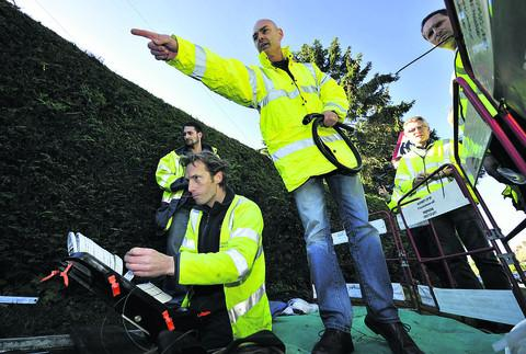 Bicester Advertiser: BT Engineer Grant Mayhook, front, works on the fibre optic broadband cables