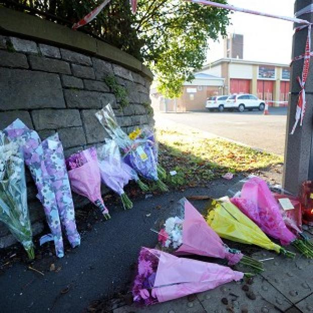 Bicester Advertiser: Floral tributes outside the Fire Station in Ely, Cardiff, where Karina Menzies, 32, was killed in a multiple hit and run incident