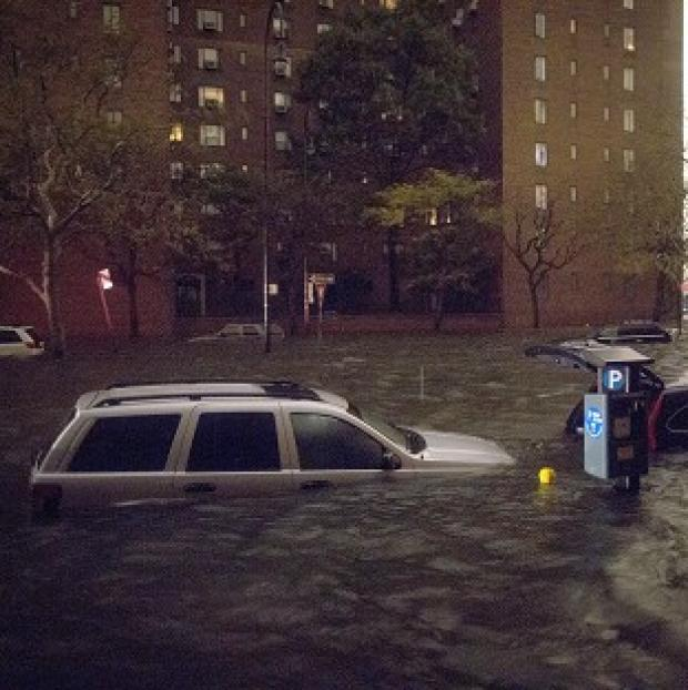 Vehicles are submerged on 14th Street near the Consolidated Edison power plant in New York (AP)