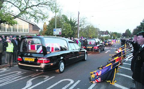 Mourners pay their respects as the hearses pass by.