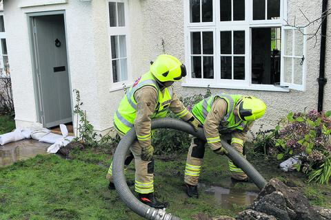 Firefighters pump water from the garden of a house in Bladon after water came up through the floorboards