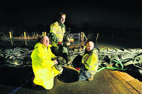 Bicester Advertiser: Flood barriers in Bullstake Close are set up by, from left, Colin Cooper, Steve Boyd and Steve Carter