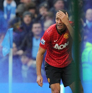 Manchester United's Rio Ferdinand holds his head after being hit by a coin at the Etihad Stadium