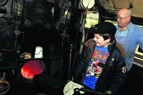 William Beard, 11, stokes the boiler of a steam engine watched by volunteer fireman Phil Marsh