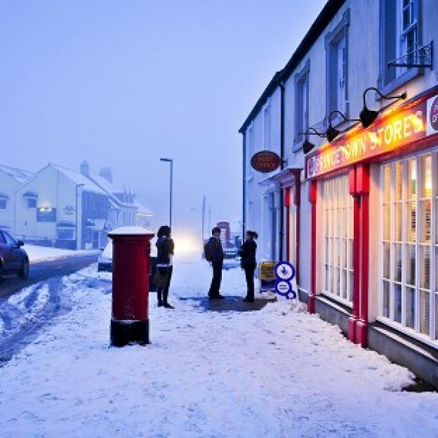 Traffic is flowing on the slushy roads and children make their way to school in Princetown, Dartmoor