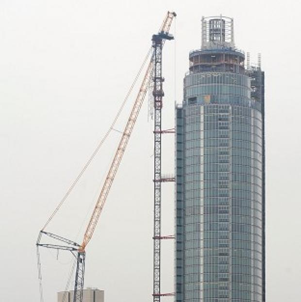 A crane (left) next to the damaged crane at The Tower at St George Wharf in Vauxhall, London, where Pete Barnes's helicopter crashed