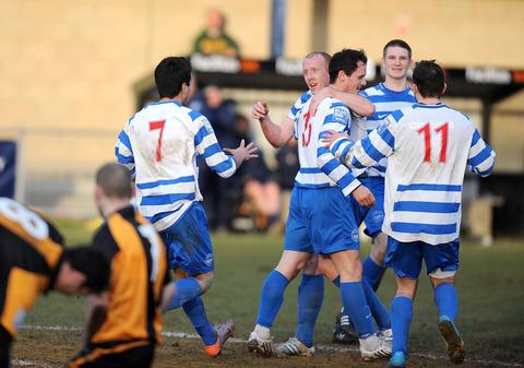 Jamie Cook is congratulated by delighted teammates after scoring Oxford City's equaliser