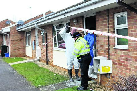 Tragedy: Police and fire investigators at the bungalow in Banbury
