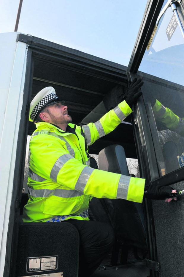 Pc Mark Pilling tests an emergency door during Operation Coachman