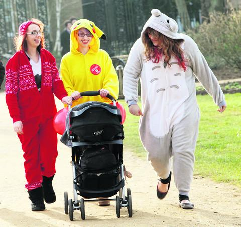 Kirsty Prowse, left, takes a walk in her onesie with twin sister Nicole, pushing her 12-week-old daughter Alexis Gill, and friend Lorna Eaton