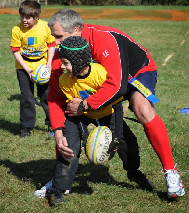 London Welsh head coach Lyn Jones puts his worries behind him as he tackles Oscar Richardson, 9, during a coaching session at Aston Rowant Primary School. It was part of the Aviva Premiership's schools community programme