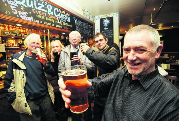 Drinkers at Far From The Madding Crowd in Oxford, including Camra's Tony Goulding, front, toast the cut in tax on beer