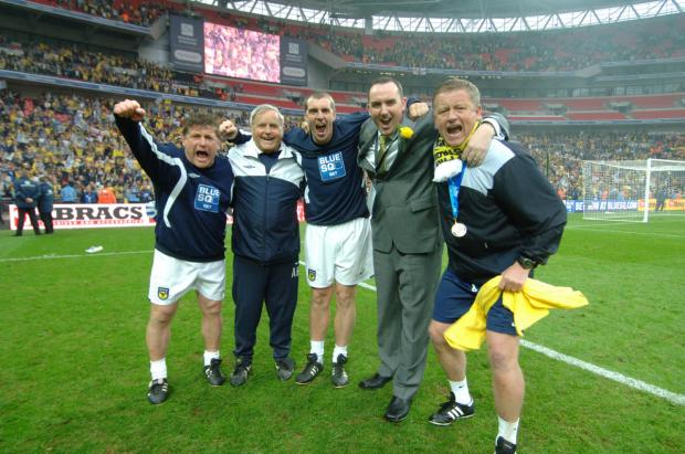 Bicester Advertiser: Chris Wilder celebrates winning promotion at Wembley with his backroom team and chairman Kelvin Thomas