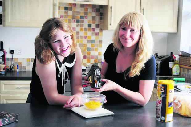 Evie Cousins weighs out pasta with her mum Emma Anderson – controlling your diet is crucial to coping with diabetes