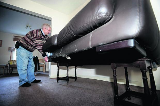 Bicester Advertiser: Andrew Ivett checks his sofa placed on tables as flood waters rise around his home in Earl Street