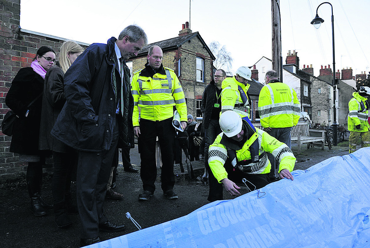 Environment Secretary Owen Paterson is shown the flood defences at Oxford's Osney Island by Al Wells of the Environment Agency
