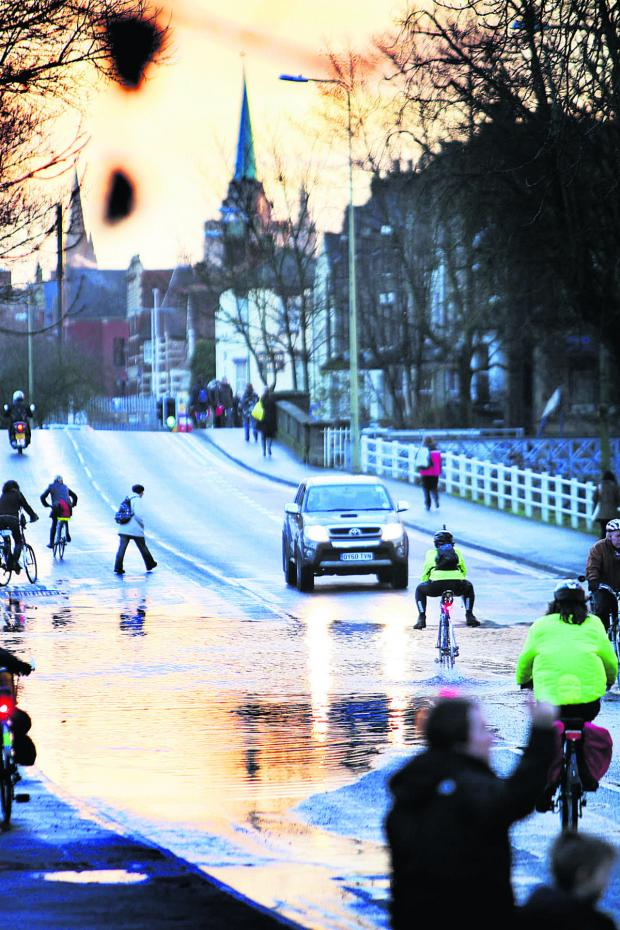Bicester Advertiser: One of the few cars to brave Botley Road waits as a cyclist goes through the floods, legs held up to avoid a soaking