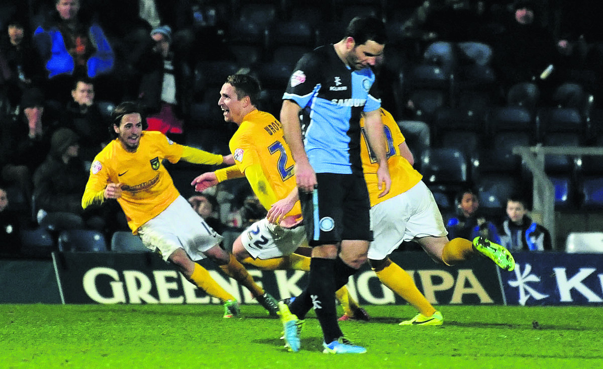 Nicky Wroe races off to the Oxford United fans after his late winner at Wycombe, chased by Ryan Williams (left) and Deane Smalley