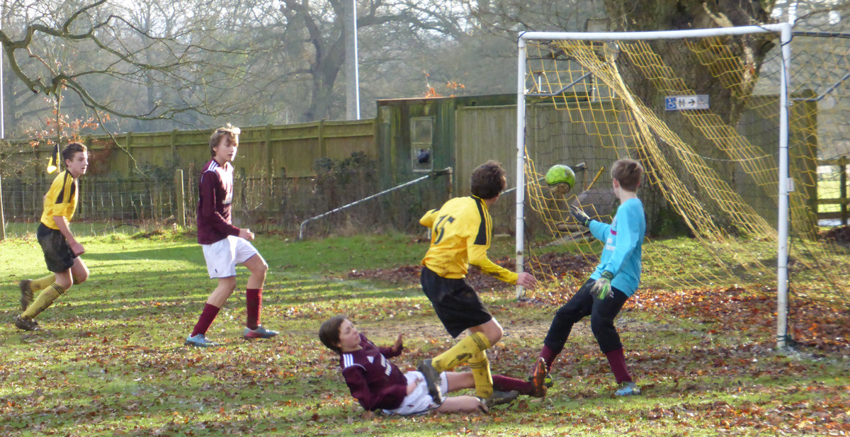 Ryan Holmes (15) scores one of North Leigh's goals in their 11-1 home win against Bourton Rovers Youth in the Under 14 A League encounter, despite a strong challenge from a visiting defender