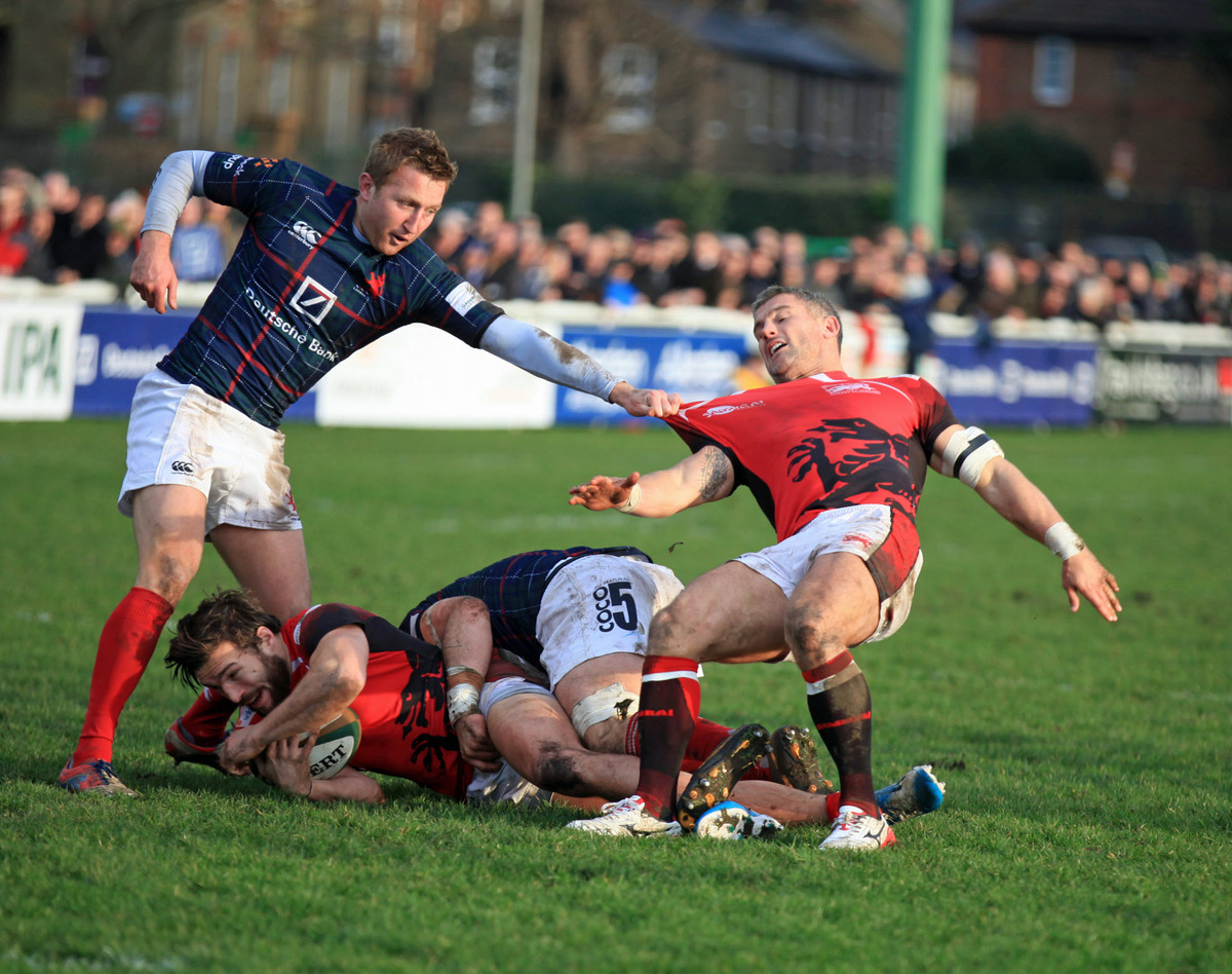 London Welsh captain Tom May (right) is stopped unconventionally against London Scottish, while teammate Seb Stegmann is tackled in more traditional style