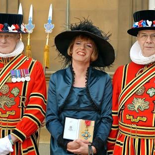 Artist Grayson Perry holds his CBE presented to him by the Prince of Wales d