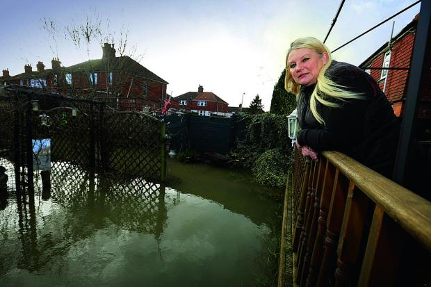 Bicester Advertiser: Jayne Madden surveys her flooded garden in Weirs Lane, off Abingdon Road, Oxford.
