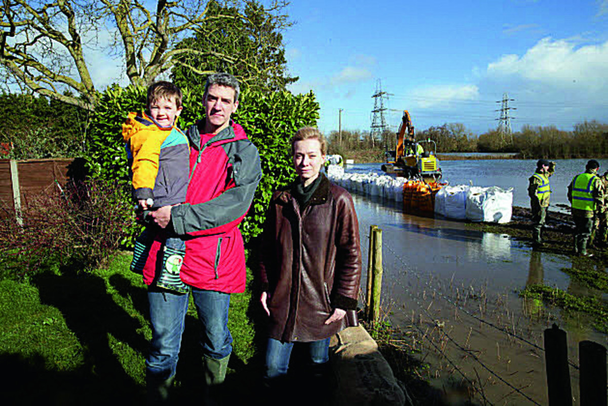 Nicola Blackwood MP views progress on South Hinksey's flood barrier in the garden of Adrian Porter pictured wit