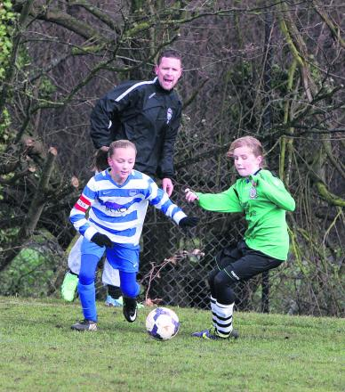 Oxford City Under 12's Tegan Partlett steams past Kidlington's  Mai Thomson while City manager Jason Partlett looks on