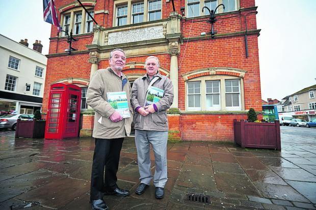Bicester Advertiser: Councillors Mike Dyer, left, and David Bretherton, who led on the Thame Neighbourhood Plan, pictured with the approved document in front of the Town Hall. Picture: OX65635 Cliff Hide
