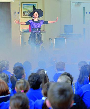 Charlton-On-Otmoor Primary School pupils watch as dance teacher Sissi Tellechea appears out of a cloud of dry ice on Monday to start World Book Week at the school. Pictures: OX65671 Simon Williams