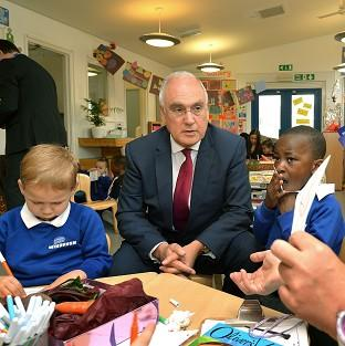 Bicester Advertiser: Sir Michael Wilshaw, Ofsted chief inspector, with Rhys Lockyer, left, and King Akingbulu during his visit to the Windrush Nursery in Woolwich, prior to the Ofsted Early Years Annual Report being published