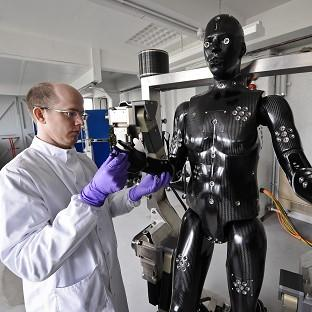 Jaime Cummins checks the Porton Man robot mannequin that will help test the next generation of chemical and biological suits for the UK's