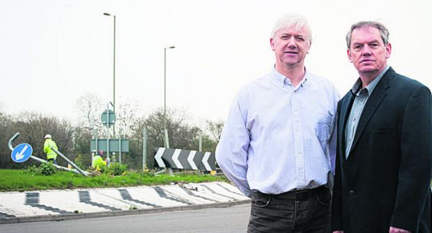 Nick Cotter, left, and Les Sibley at the Vendee Drive roundabout, which keeps being hit by cars