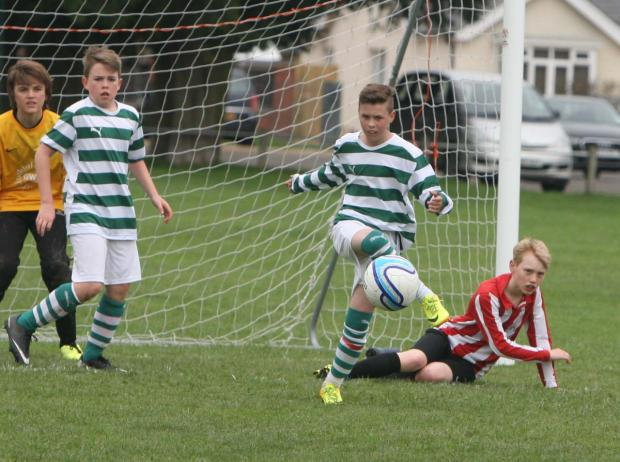 Didcot's Nathan Sandland clears the ball during his side's Under 12 Spring A League clash with Summertown
