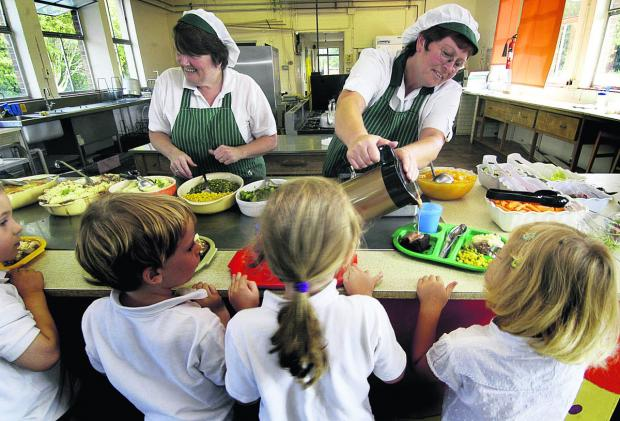 Dinner ladies Carole Butler, left, and Julie White with pupils at Wantage