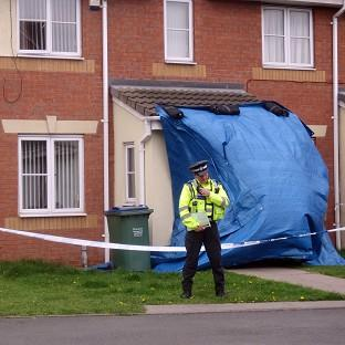 A police officer outside a property in Tividale, near Tipton where a 19-year-old woman was doused in high-strength cleaning fluid
