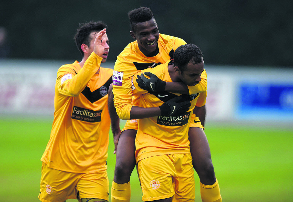 Oxford City's Darren Mullings is mobbed after firing them ahead against Brackley Town