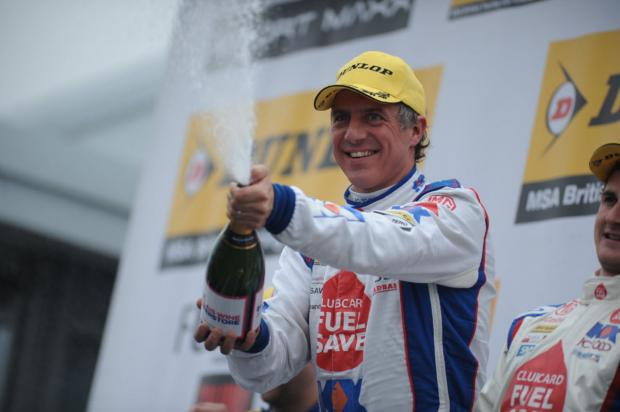 Jason Plato celebrates with champagne after his win in the first race