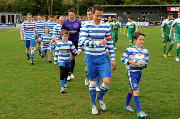 Steve Basham leads Oxford City out on his final appearance for the club accompanied by his son, Joseph