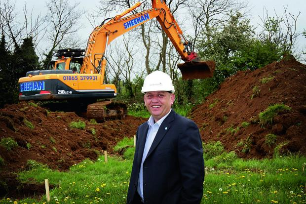 Bicester Advertiser: Project director Steve Hornblow watches bulldozers start work on the eco town