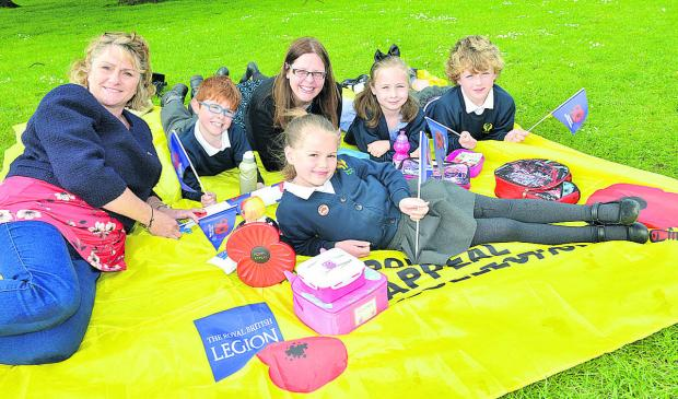 Laura Towell, left, Royal British Legion community fundraiser for Oxfordshire, and Bure Park School, Bicester, year five teacher Tina Woodgate with pupils, from left, Courtney Etheridge, seven, Dylan Morgan, seven, Lily Clare,