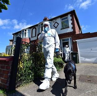 Bicester Advertiser: A forensic officer with a dog outside a house in North Shields which is being searched by police