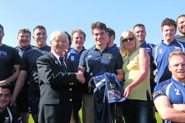 Bicester Advertiser: Oxfordshire RFU president Ken Bumpass receives a county shirt sponsored by the Jim Douglas Memorial Fund from the late Harwell player's son Rob (centre) and partner Mandy Evans. It was the Douglas family's wish to support Oxfordshire rugby and put the