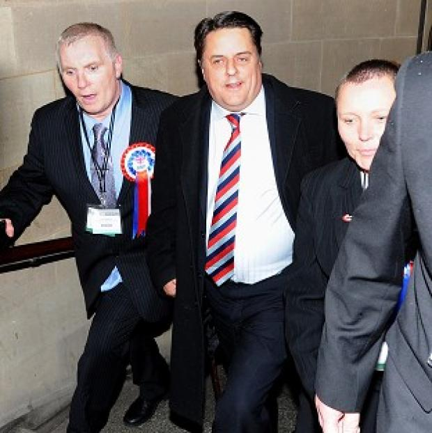 Bicester Advertiser: BNP leader Nick Griffin (centre) arrives at the European Parliamentary elections count at Manchester Town Hall