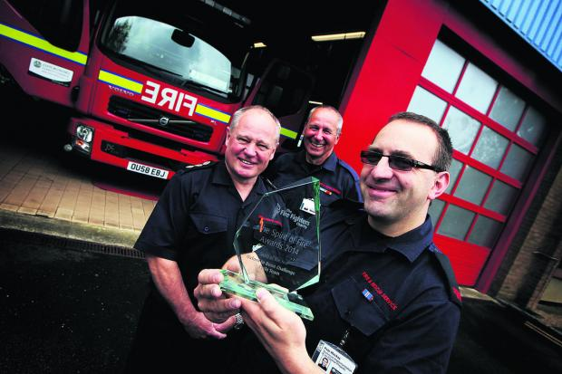 Firefighter Pete MacKay holds the award with station manager Simon Sumners, le