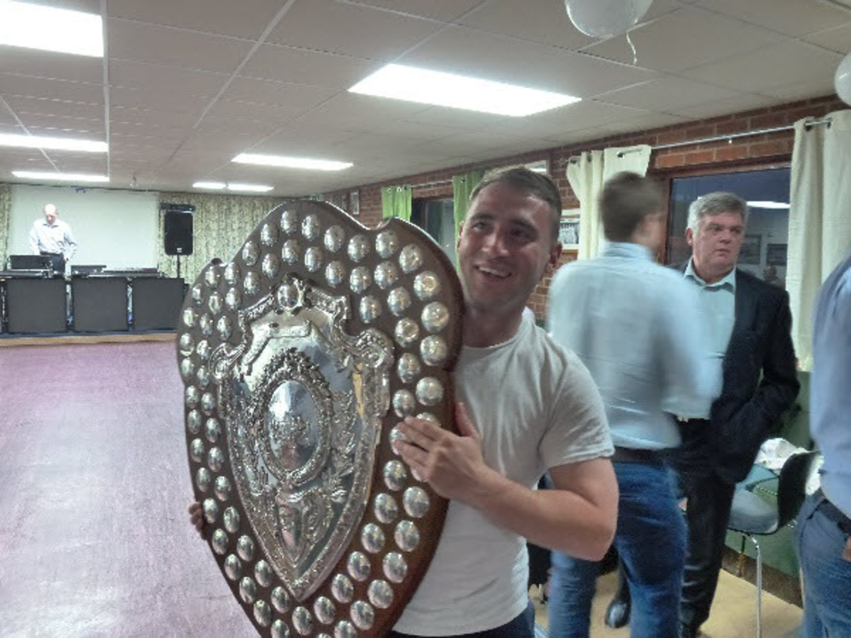 Wantage Town striker Matt Pedder, who has agreed a new contract, holds up the Hellenic League championship trophy at the club's presentation night
