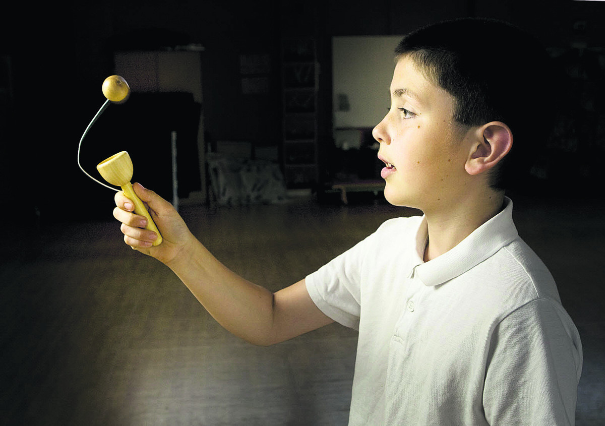 Tristan Mattews, 11, plays with a traditional toy at the Soldiers of Oxf