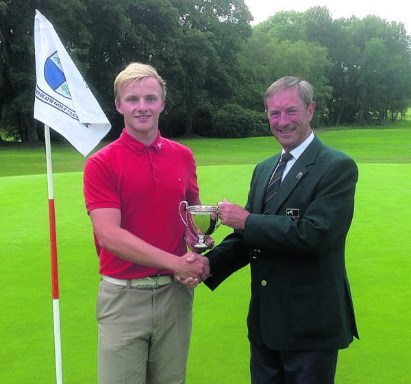Jake Dines receives the club championship trophy from Frilford Heath captain Gordon Neilson after winning a play-off